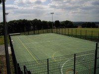Rebound fencing, polymeric surfacing and floodlights for a multi use games area